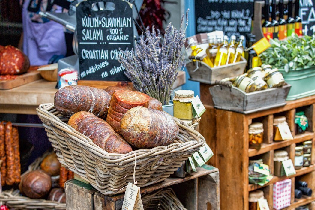 Photo of a food stall at Borough Market with a basket of Slavonian salami on prominent display.