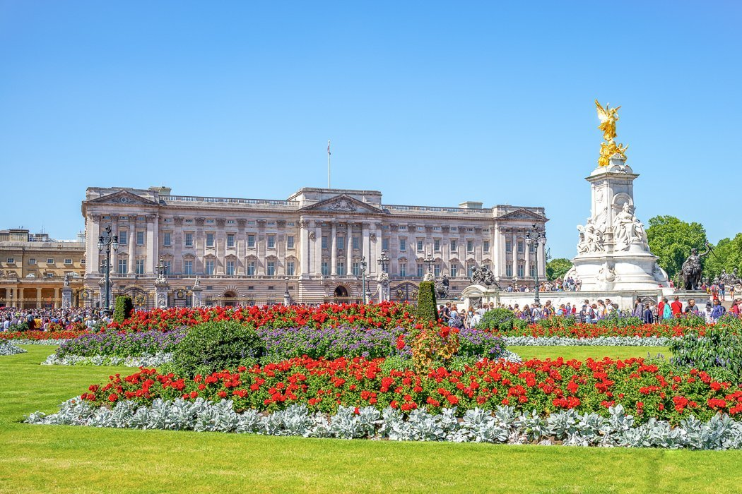 Photo of Buckingham Palace with the striking red tulip garden in the foreground cleverly obscuring the throngs of tourists.