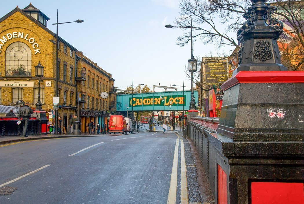 Photo of the road leading to Camden Lock Market with the turquoise railway bridge in the center and yellow-brick houses on the left-hand side.