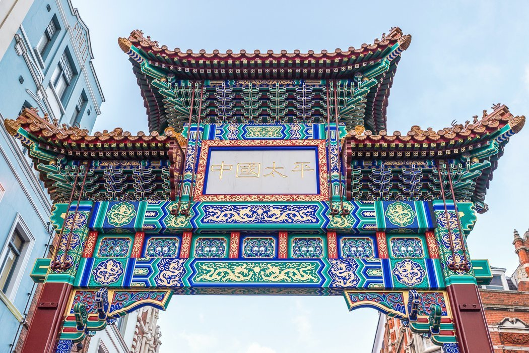 """Low-angle shot of the colorful gate in Chinatown, London. Designed in the style of the Qing dynasty, the Chinese characters on the front translate to """"China, Peace, Security""""."""