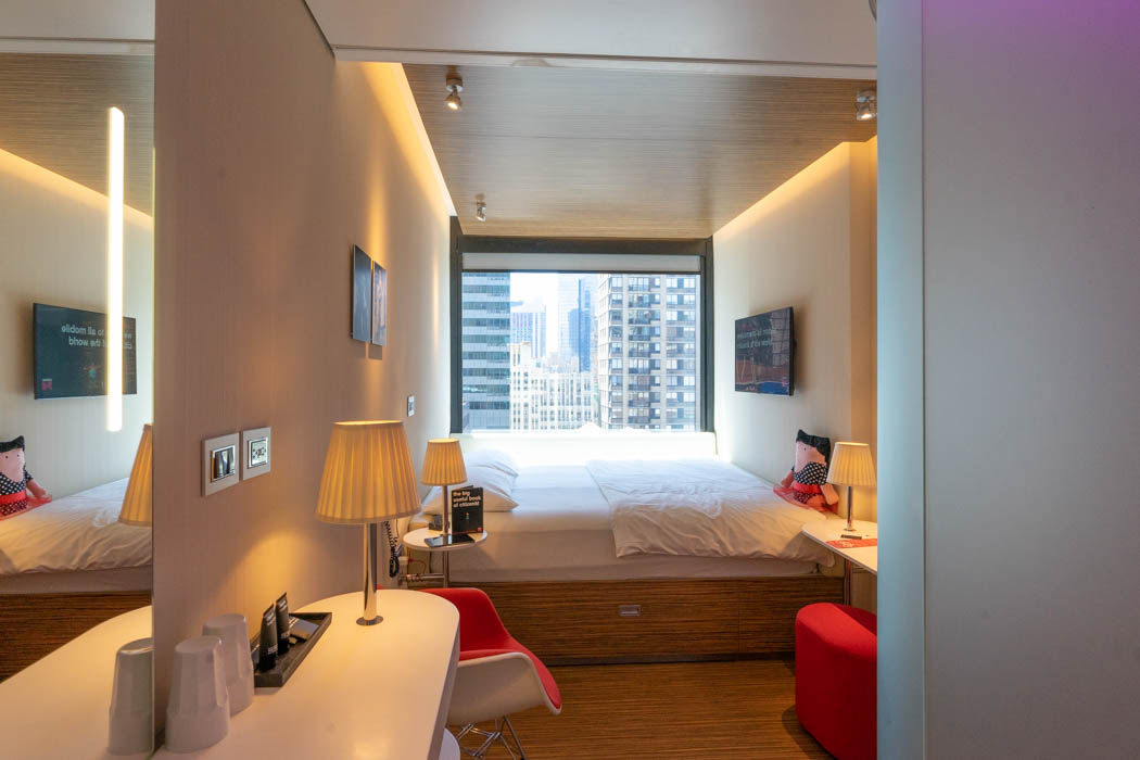 Photo of a standard CitizenM hotel room, the décor is clean, bright, and modern, the bed generously sized and inviting, the view from the large picture window spectacular.