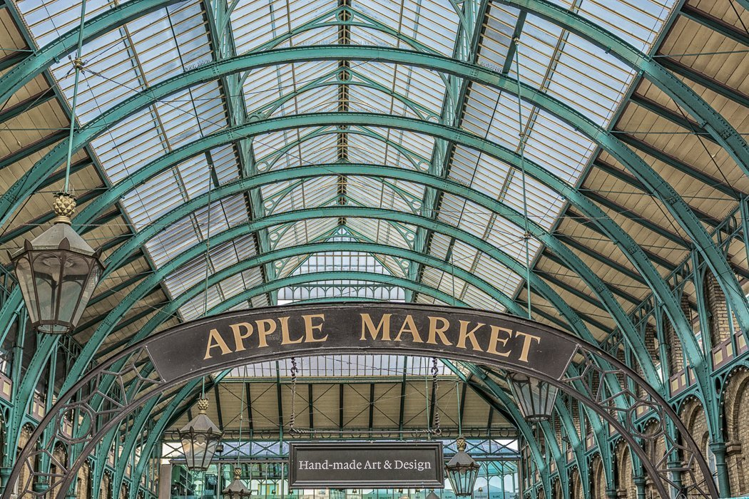 Photo of Apple Market in Covent Garden showing the market sign and an array of blue-green metal arches supporting the ceiling.