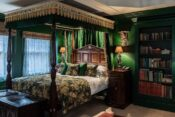 Photo of a hotel room at The Rookery in London featuring a luxurious four-poster bed, antique hardwood furniture, and dark green walls.