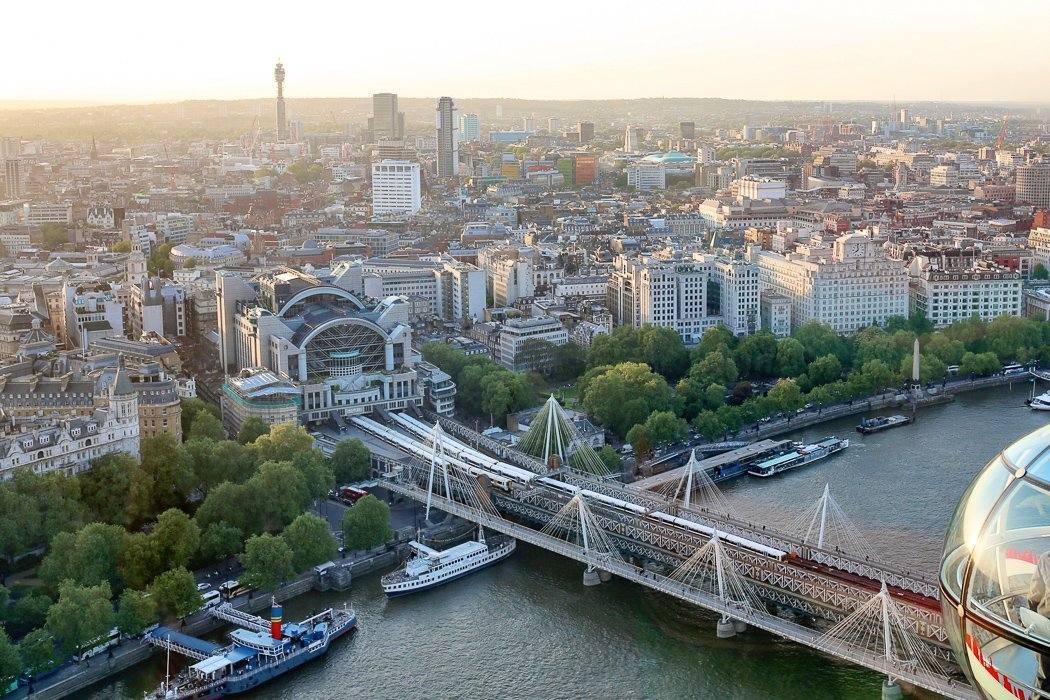 Panoramic shot of London's skyline taken from one of the capsules of the London Eye, focusing on Charing Cross station and Hungerford Bridge.