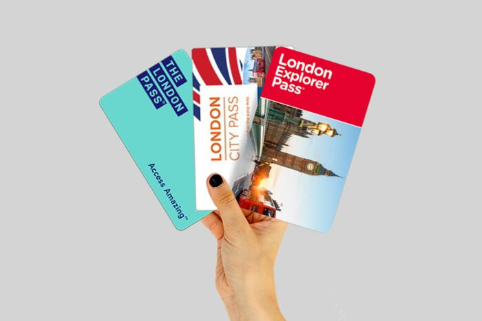Hand holding a selection of London city passes.