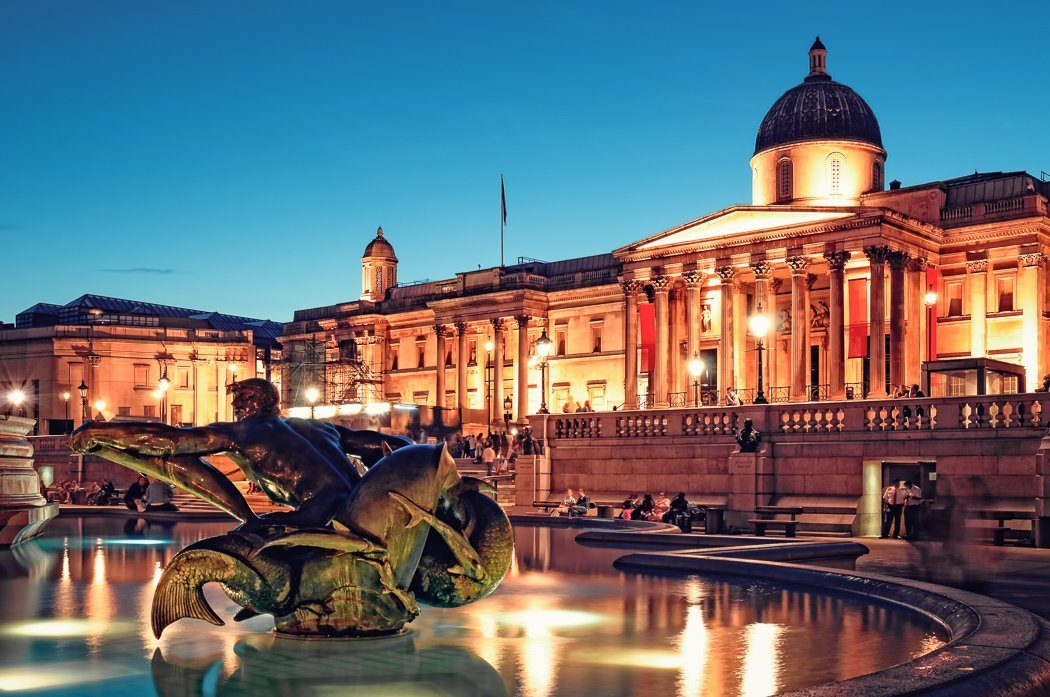 Photo of the National Gallery on Trafalgar Square in the evening, with a statue of a merman in the foreground, the brightly lit building reflected in the fountain.