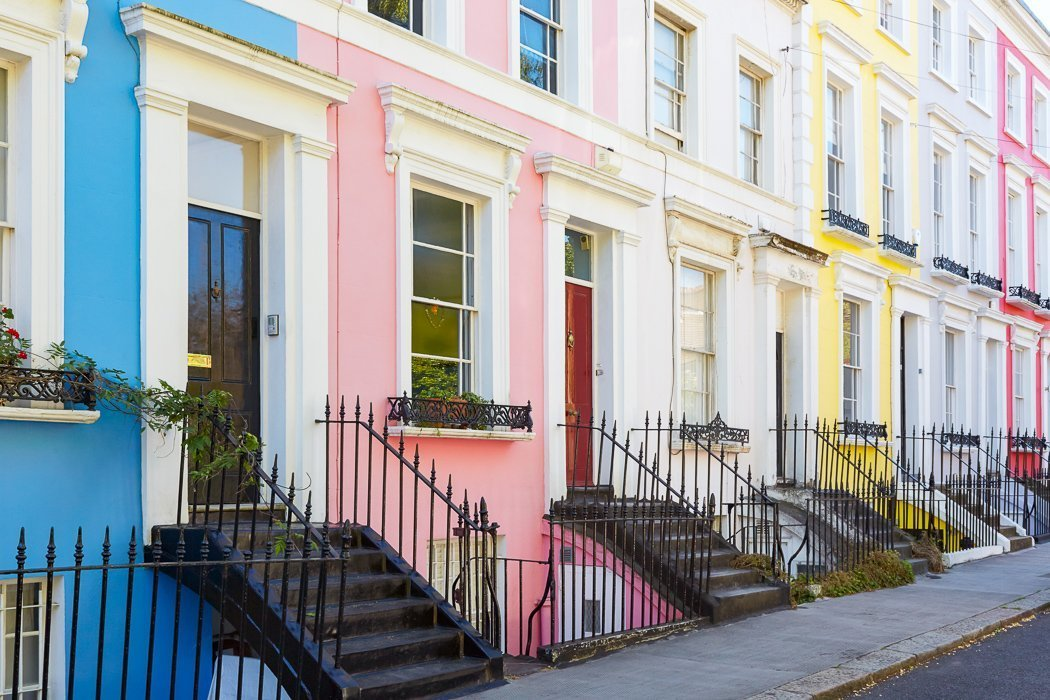 Photo of a row of pastel-colored houses in Notting Hill, London.