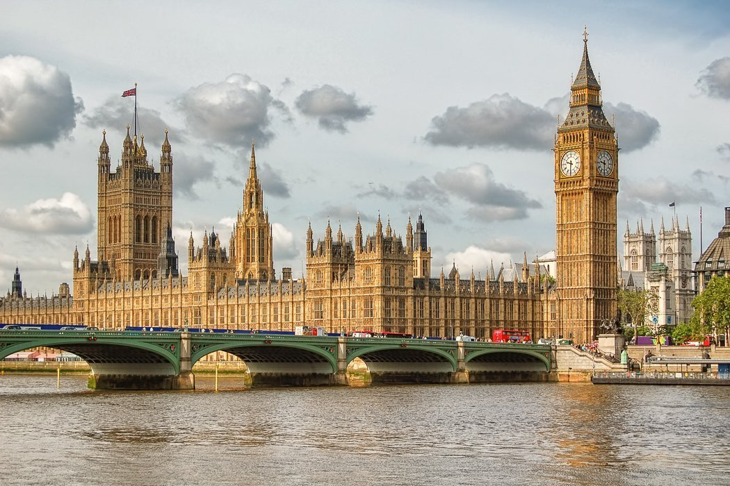 Photo showing Big Ben, London's iconic landmark, towering above the Palace of Westminster with the River Thames in the foreground.
