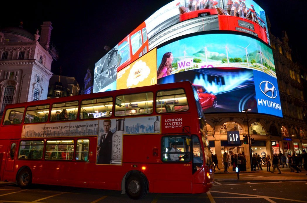 Nighttime photo of Piccadilly Circus, showing an iconic double-decker bus passing an enormous LED billboard.