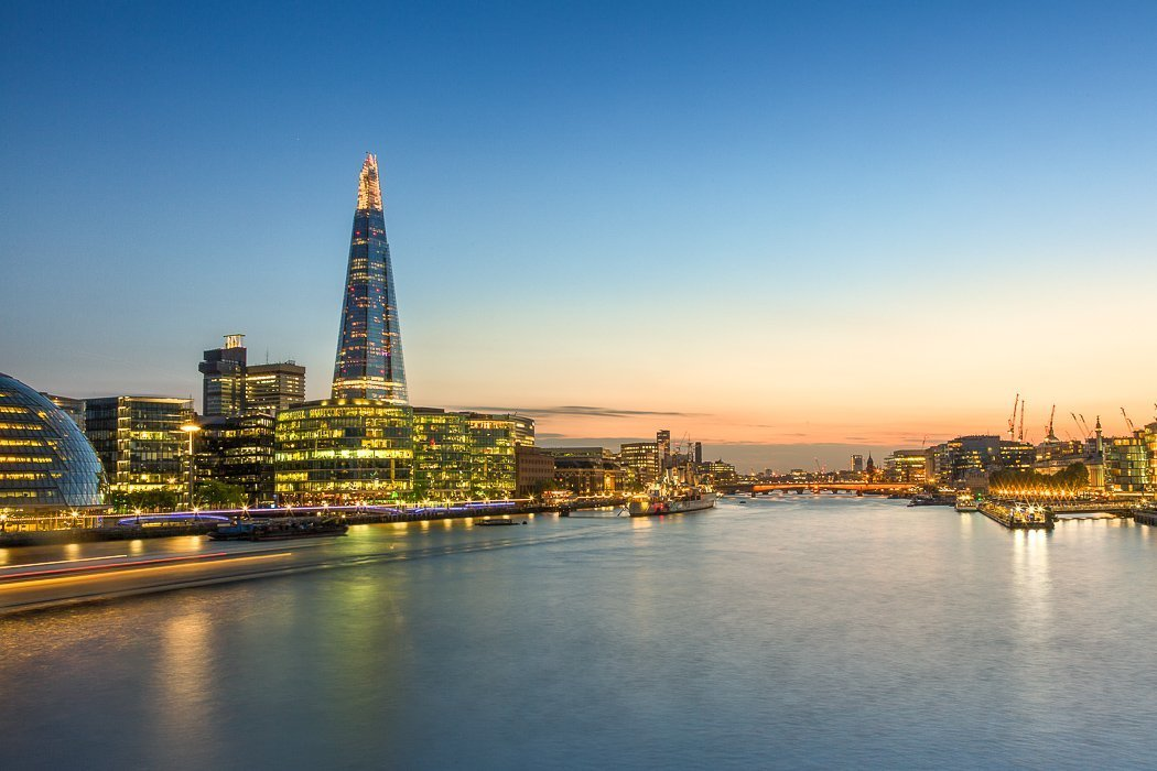 Panoramic photo of the Thames at dusk, with the Shard towering above the illuminated skyline on the left bank.