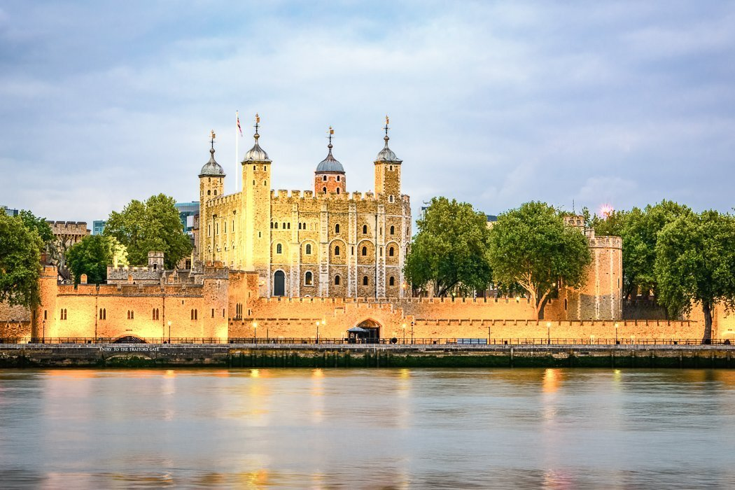 Photo of the Tower of London at dusk from across the Thames, eerily illuminated by the golden glow of riverside streetlights.